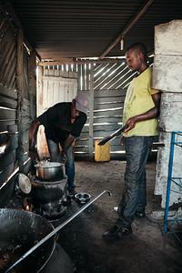 Cooks preparing posho (cornmeal porridge) to accompany a pig roast at a restaurant in Walukuba.