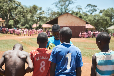 Jay Jay, X-SUBA's head soccer coach, hands out bibs during a school sports tournament day.  The local schools can't afford uniforms or balls for the children, so X-SUBA rotates through the different schools each day of the week to provide these items for sports programs.