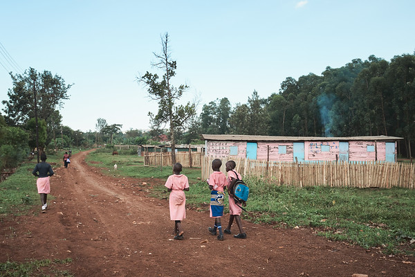 Children walking past a nursery school in Walukuba, Uganda, on one of the village's main roads.