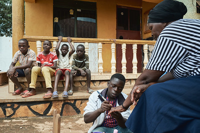 International Women's Day in Uganda is all about the men treating women like queens.  Here, a young man provides manicures and pedicures to women in Walukuba during X-SUBA's Women's Day celebration.  Younger boys from the Learning Center look on.