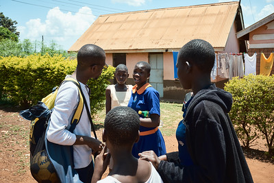 """Kenneth, co-founder of X-SUBA, chats with some girls that participate in his sports programs as he walks through the streets of Walukuba.  Kids yell """"coach, coach!"""" everywhere he goes, wanting to share with him what is going on in their lives."""