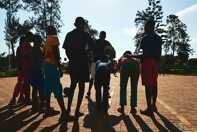 Coach Steve introducing boys to the game of basketball during X-SUBA's Connection Day.  Every Saturday, youth in the community meet at a local church to play sports and engage in life skills lessons led by X-SUBA coaches.