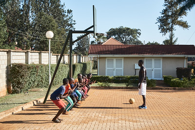 Coach Steve introducing basketball to some boys during X-SUBA's Connection Day.  Every Saturday, youth in the community meet at a local church to play sports and engage in life skills lessons led by X-SUBA coaches.