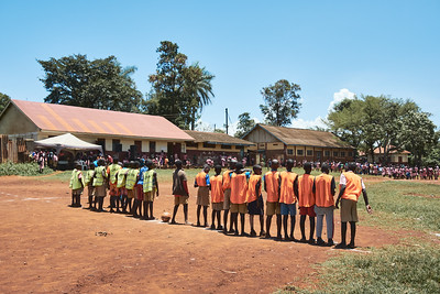 Students participating in a school sports tournament line up before a soccer match.  The school doesn't have proper bibs or good soccer balls, so X-SUBA coaches were there to provide them.
