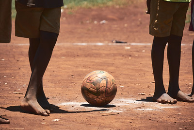 Bare feet awaiting kickoff during a school sports tournament in Walukuba.  The ball was provided by X-SUBA, as well as the bibs, but shoes are up to the students.