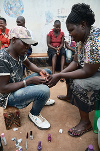 A young man providing a manicure during International Women's Day.  This day is sacred in Uganda and the women are treated accordingly.