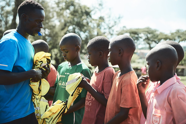 Coach Jay Jay handing out bibs to students during a school sports tournament.  The only sports uniforms in town are X-SUBA's donated bibs, which they bring to different schools on different days of the week.