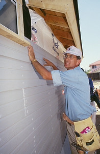 Millard Fuller hanging vinyl siding on a Habitat house. (Jimmy Carter Work Project 1995)