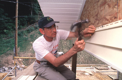 Millard Fuller, founder and president of Habitat for Humanity, applies vinyl siding on a house during the '97 Jimmy Carter Work Project in Tennessee, USA. (1997)