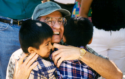Millard Fuller hugs two children in Costa Rica. (1999)
