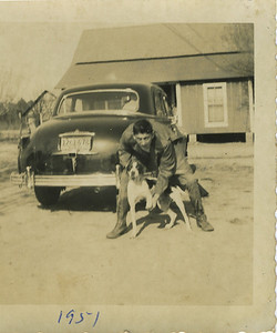 Millard, age 16, with hunting dog. He often went hunting for rabbit, squirrel and opossum. He also raised rabbits to sell to restaurants.