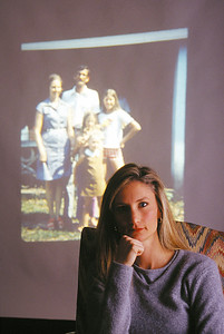 2000 Faith Fuller, daughter of Millard and Linda Fuller and Senior Producer with Habitat for Humanity International, pictured with an early photo of her family projected onscreen in the background.