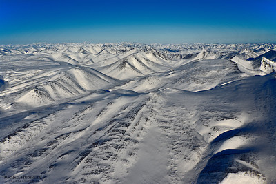 The eastern side of the Brooks Range in Canada's Yukon territory seen during this morning's descent into the survey area over sea ice in the eastern Beaufort Sea. The seemingly endless number of mountain peaks provides a sense of the vastness of the Arctic environment.