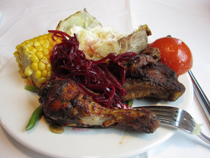 BBQ dinner, with chicken, ribs, corn on the cob, beet salad, baked potato and roasted tomato