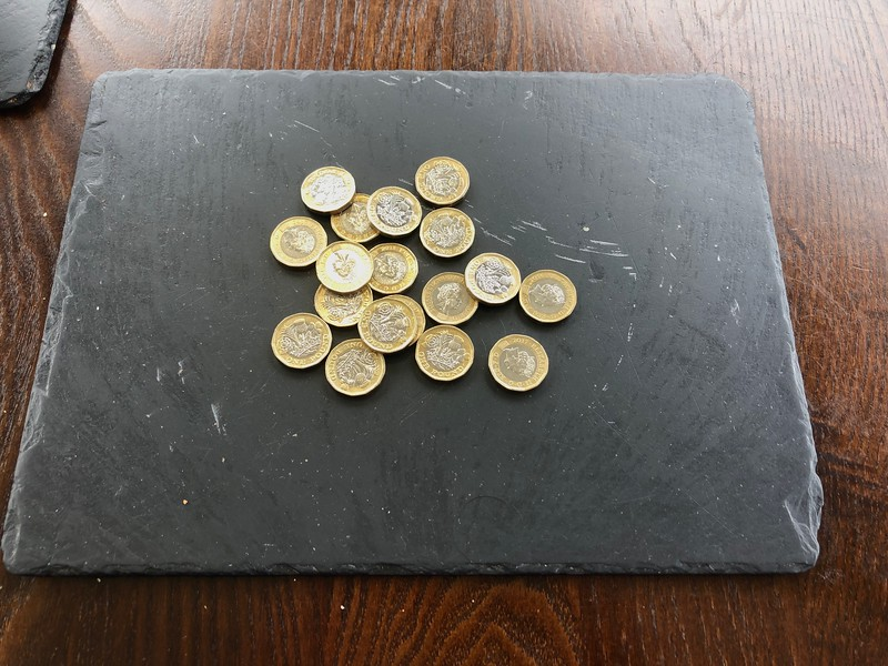 Slate place mat.<br /> One pound coins for use later at an automated scuba tank fill station.<br /> Holly Tree Hotel, Loch Linnhe, Scotland