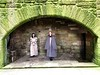 Tour guides standing in the main kitchen fireplace<br /> Linlithgow Palace, Linlithgow, Scotland.