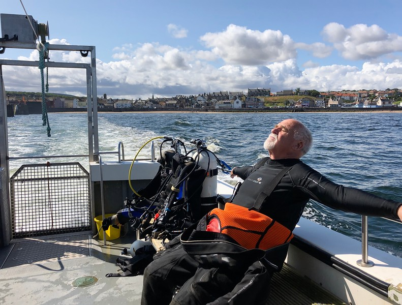 Jim enjoying the sunshine. <br /> Heading out for dives #8 & #9.<br /> Eyemouth Harbor, Scotland.