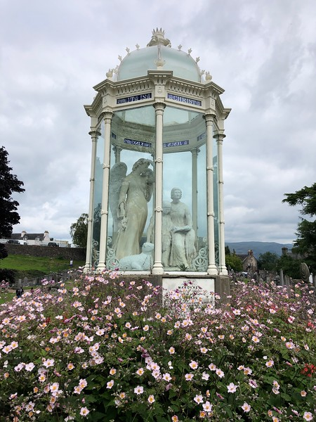 """The enclosed figures represent the traditional story of Margaret Wilson who, aged 18, was executed by drowning in the Solway Firth for refusing to renounce her Protestant faith.""<br /> From the Old Town Cemetery website:<br /> <br /> The Martyrs Monument<br /> <br /> The three figures represent an angel keeping watch over two young girls, one of whom is reading the Bible to the other. The reader is Margaret Wilson, the listener is her younger sister Agnes. Such is the logic of legend that they are known locally as the 'Mary Martyrs'.<br /> <br /> The two girls belonged to Wigtonshire, the daughters of Gilbert Wilson, a committed Episcopalian. Despite this, the sisters were followers of the Covenanters, an extreme Presbyterian group strongly opposed to the Anglican reforms of Charles II. Margaret and Agnes, aged 18 and 13 respectively, were arrested for their beliefs and along with Margaret McLauchlan, an elderly neighbour, tried for and found guilty of high treason. All three were sentenced to death by drowning. Agnes's father was able to buy her freedom but despite a temporary reprieve the others were led to a point below high water mark on the treacherous Solway Firth, tied to stakes, and left to drown in the incoming tide. Margaret McLauchlan, by then in her late 60s, had no resistance to the powerful current and soon succumbed to its force. Margaret Wilson was offered her freedom, but refused to relinquish her convictions and died for her faith on May 11th 1685."