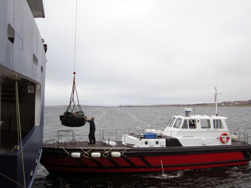 Boat delivering passenger luggage.<br /> Port Stanley, East Falkland Island.