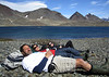 Trekkers, Jeff, Lilian & Nico, taking a respite beside a mountain lake.<br /> Trail from Fortuna Bay to Stromness.<br /> South Georgia Island.