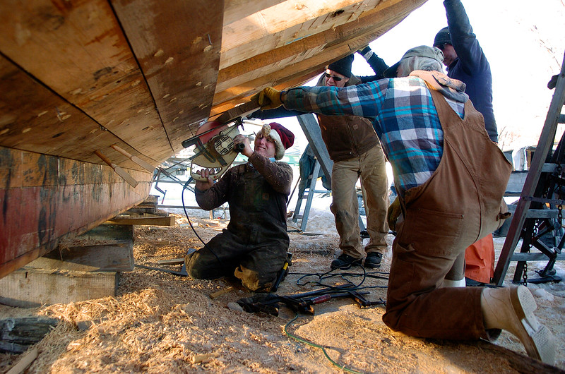Wicked Local Photo by Nicole Goodhue Boyd 021111<br /> Burnham trims a board on the underside of the  new schooner Pinky Ardelle  Friday February 11, 2011 at  Burnham Boatbuilding.