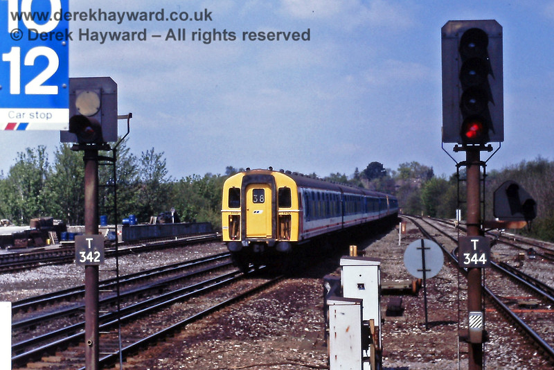 1110 heads a Down train into Haywards Heath on Saturday 28.04.1990.  Note that signal T342 showed a permanent red signal, but that departures and shunts to the north were permitted from the Down Slow line via signal T344.  Among other things this allowed access to the sidings and for goods train moves towards the Ardingly Branch.  Eric Kemp retains all rights to this image.