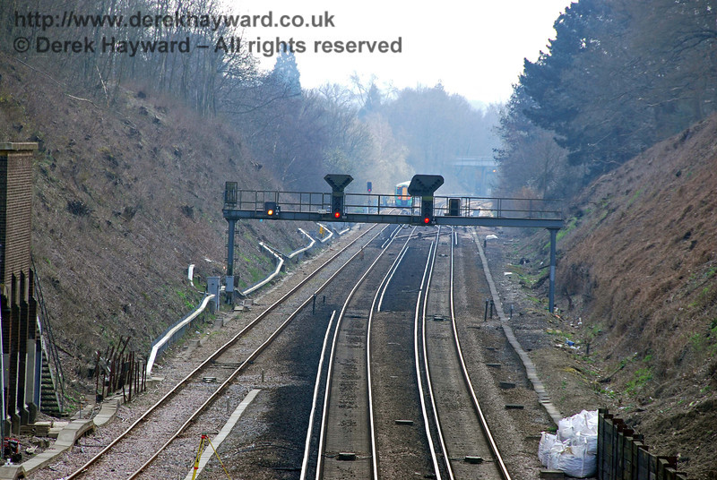 Copyhold Junction, looking south with a long lens.  The two main signals control the main line, with a permanent yellow colour light for the goods line.  The main signal for the goods line is beyond the gantry.  27.03.2007