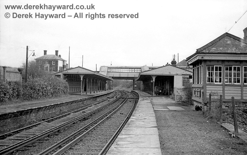 Ardingly Station captured on 12 April 1965 in some images taken by John Attfield.  John retains all rights to these images but has kindly allowed me to use them on my site.  This shot looks east along the platforms towards the footbridge.  The signal box is on the right and largely conceals the main buildings at the station entrance, which are in the right upper section of the photo.