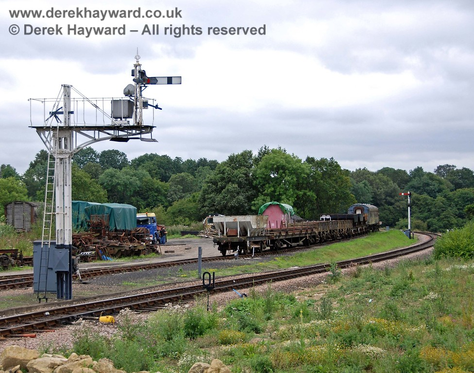 On the left the reverse side of the northbound Inner Home signal at Horsted Keynes controls trains from Sheffield Park, whilst in the distance the southbound Advance Starter stands just beyond the end of the sidings. 15.08.2009