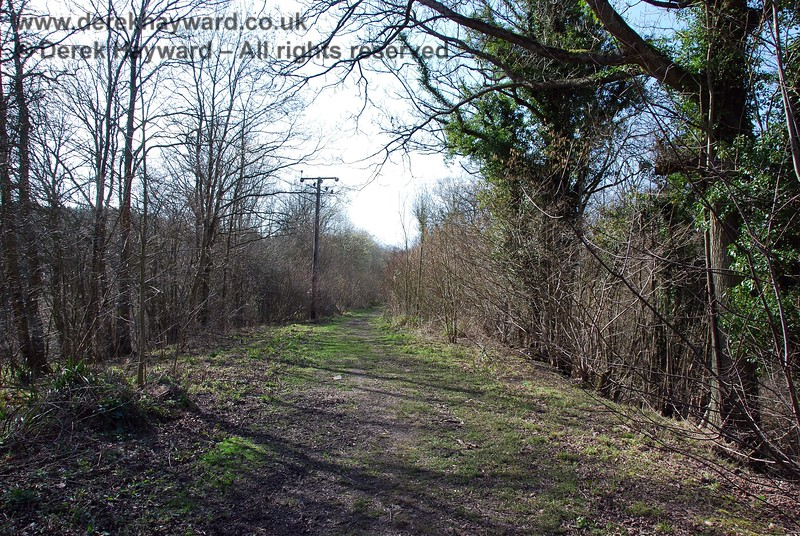 The power lines turn west on entering the trackbed and follow the route of the track.  This view looks west.  It can been seen that the route remains fairly clear.