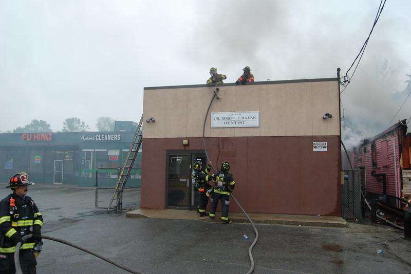 Firefighters work off building next door