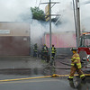 Firefighters work to protect exposure building