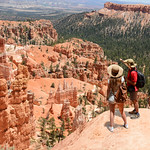 Couple on hiking trip enjoying beautiful  mountain landscape,  Friends relaxing on top of the mountain.  Bryce Canyon National Park, Utah, USA.