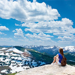 Girl sitting  on the rock on hiking trip in beautiful mountains. Snowy peaks and green meadows and hills View from Trail Ridge Road. Rocky Mountains National Park. Close to Estates Park,Colorado, USA.