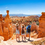 Family standing next to Thor's Hammer hoodoo on top of  mountain looking at beautiful view. Bryce Canyon National Park, Utah, USA