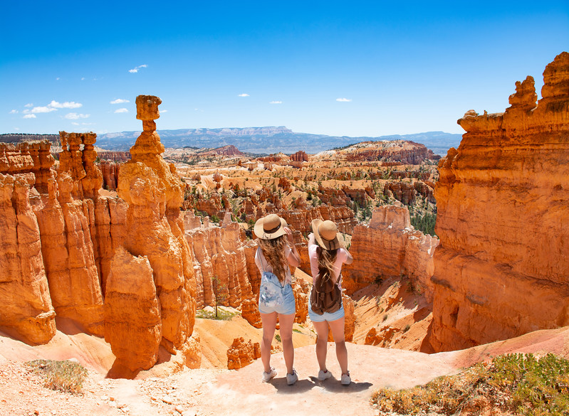 Girls on vacation hiking trip. Friends standing next to Thor's Hammer hoodoo on top of  mountain looking at beautiful view. Bryce Canyon National Park, Utah, USA