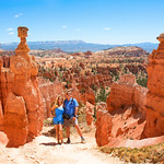 People enjoying summer hiking trip <br /> standing next to famous Thor's Hammer hoodoo. Smiling happy  couple embracing on vacation in the red mountains. Bryce Canyon National Park, Utah, USA