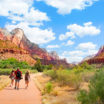 Couple on hiking trip in the red mountains walking on pathway on summer vacation. Zion National Park, Utah, USA