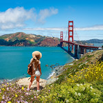 Girl looking at beautiful summer coastal landscape, on hiking trip. Woman relaxing on mountain. Golden Gate Bridge, over Pacific Ocean and San Francisco Bay, San Francisco, California, USA.
