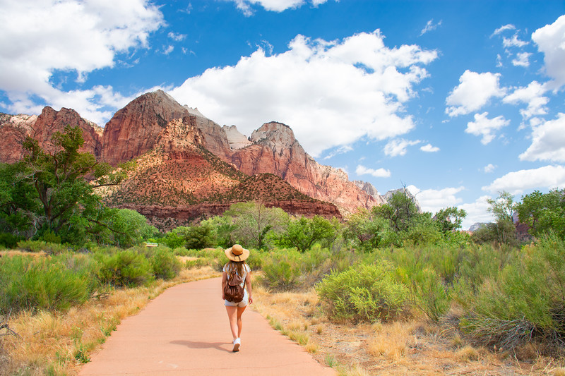 Girl on hiking trip in the red mountains, walking on pathway. Zion National Park, Utah, USA