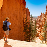 Man standing on top of the mountain taking photos with his camera.Beautiful red mountain landscape.  Bryce Canyon National Park, Utah, USA