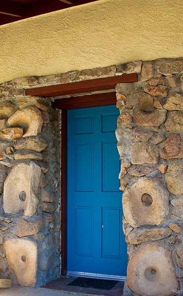 This is the entrance door of a stone house at the foot of Baboquivari Peak.  The house was built many years ago before the gathering of indian artifacts was prohibited.  Ancient metate are embedded in concrete on each side of the doorway.  If only they could speak.