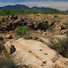 These holes in an outcrop of hard stone are called metates.  A narrow ravine can be seen immediately behind the metates.  The Santa Rita Mountains are in the background.
