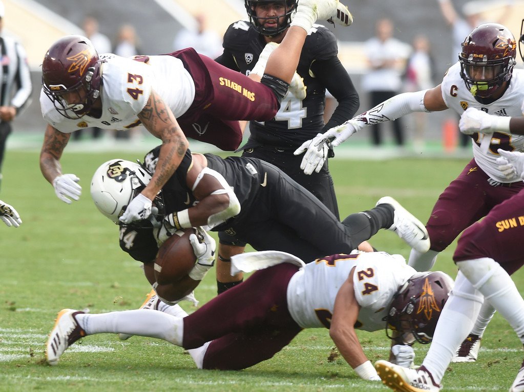 . BOULDER, CO: October 6, 2018: University of Colorado\'s Travon McMillian gets sandwiched by  ASU\'s Jalen Harvey , top, and Chase Lucas, during  the game with Arizona State on October 6, 2018. (Photo by Cliff Grassmick/Staff Photographer)