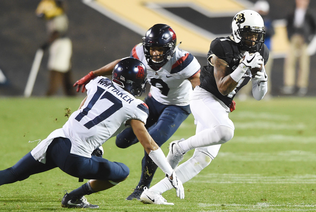 . Shay Fields, of CU, escapes Jace Whittaker and Dane Cruikshank, of Arizona, during the CU game with Arizona.  Cliff Grassmick / Staff Photographer/ October 7, 2017