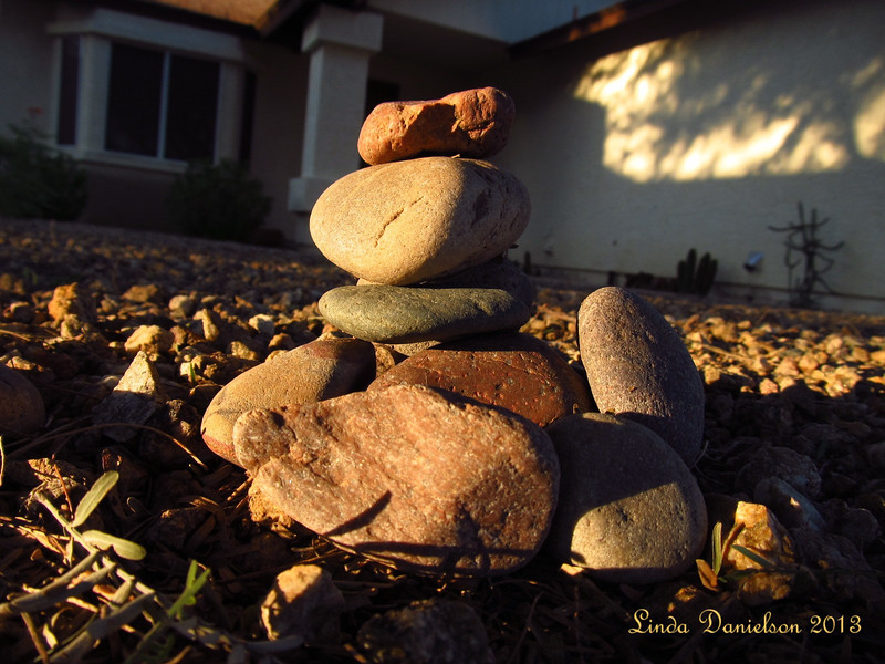 I love collecting rocks.  Every now and then, a larger rock will show up in the front yard, and I like to pile those up into ... statues or monuments, like this one that I caught with the evening sunset.