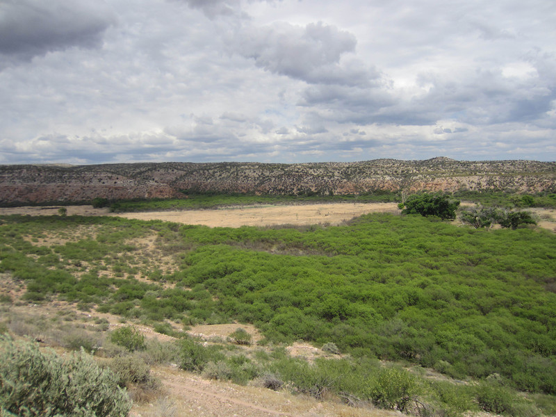 View from Tuzigoot NM. Arizona is a mining state.  Copper mining began in nearby Clarkdale and Jerome in the 1880's and produced billions in revenues. It also produced 4.5 million tons of tailings, covering 116 acres just below Tuzigoot. The tailings, which used to blow around in dust storms, were finally capped and revegetated 2006. The field on the right hand side of the picture is a rehabilitated tailings deposit from an old copper smelter.