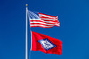 The American and Arkansas state flag flying against a clear blue sky.