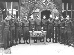 <font size=3><u> - Army Cadet Group with Trophies - 1943/44 - </u></font> (BS0201)  Army Cadet Force. Silver cups for .22 rifle shooting on range. Members came from Benson & Watlington. Photo in front of Headmasters classroom of Benson CofE Primary School.