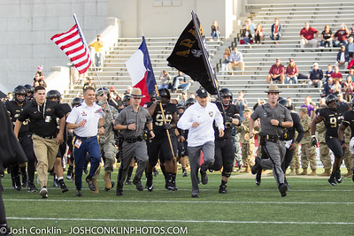 Army football coach Jeff Monken (center) leads the team out on the field prior to the game. Cordarrell Davis (left) carries out the Texas state flag at Michie Stadium in West Point, NY. Josh Conklin/For the Times Herald-Record